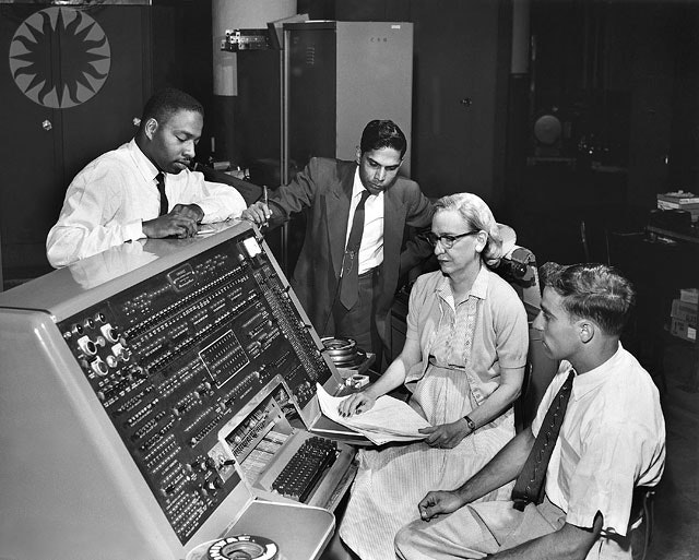 <i>SI Neg. 83-14878. Date: na.</i>  Grace Murray Hopper at the UNIVAC keyboard, c. 1960. Grace Brewster Murray: American mathematician and rear admiral in the U.S. Navy who was a pioneer in developing computer technology, helping to devise UNIVAC I. the first commercial electronic computer, and naval applications for COBOL (common-business-oriented language).   Credit: Unknown (Smithsonian Institution)