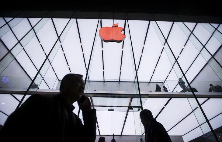 People walk past below an Apple logo in red marking the World AIDS Day, at an Apple store in Hangzhou, Zhejiang province, China, December 1, 2015. Picture taken December 1, 2015. REUTERS/China Daily CHINA OUT. NO COMMERCIAL OR EDITORIAL SALES IN CHINA - RTX1WRDP