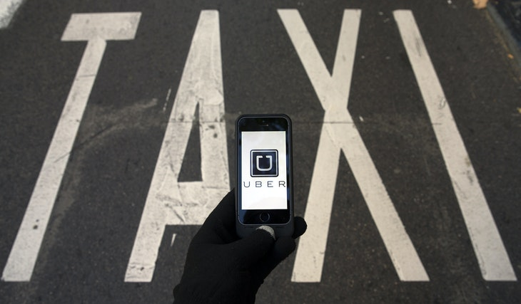 The logo of car-sharing service app Uber on a smartphone over a reserved lane for taxis in a street is seen in this photo illustration taken in Madrid on December 10, 2014. A Madrid judge has ordered U.S.-based online car booking company Uber to cease operations in Spain, the latest ban on the popular service. Taxi drivers around the world consider Uber unfairly bypasses local licensing and safety regulations by using the internet to put drivers in touch with passengers.  REUTERS/Sergio Perez  (SPAIN - Tags: LAW TRANSPORT BUSINESS TELECOMS SCIENCE TECHNOLOGY TPX IMAGES OF THE DAY LOGO) - RTR4HGT3