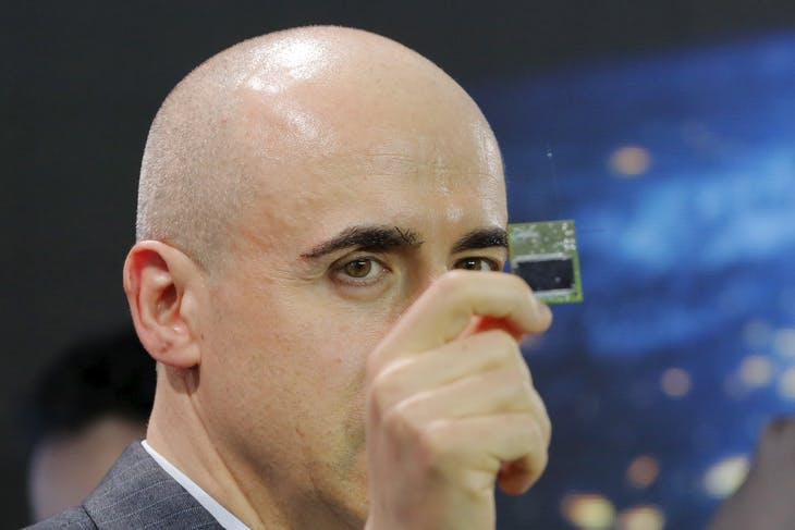 Investor Yuri Milner holds a small chip during an announcement of the Breakthrough Starshot initiative with physicist Stephen Hawking in New York