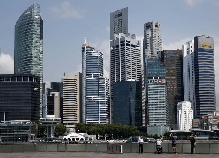 People take photos of the skyline of the central business district in Singapore