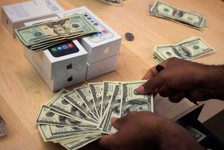 A cashier counts U.S. dollars next to five new Apple iPhone 5S phones at the Apple Retail Store on Fifth Avenue in Manhattan, New York September 20, 2013. Apple Inc's newest smartphone models hit stores on Friday in many countries across the world. REUTERS/Adrees Latif   (UNITED STATES - Tags: BUSINESS TELECOMS) - RTX13SFW