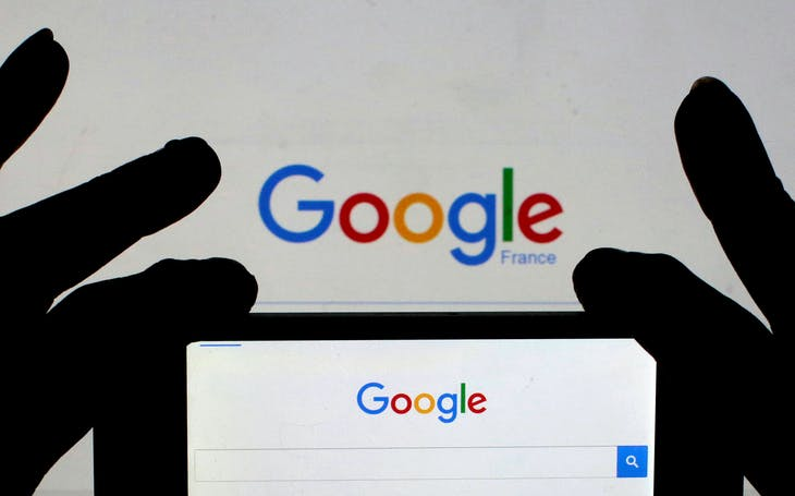 A woman holds her smart phone, which displays the Google home page, in this picture illustration taken February 24, 2016.  REUTERS/Eric Gaillard/Illustration/File Photo - RTSIYN6