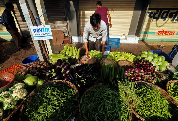 An advertisement board of Paytm, a digital wallet company, is seen placed at a roadside vendor's stall as he arranges vegetables in Mumbai, India, November 19, 2016. Picture taken November 19, 2016. REUTERS/Shailesh Andrade - RTSTQTQ