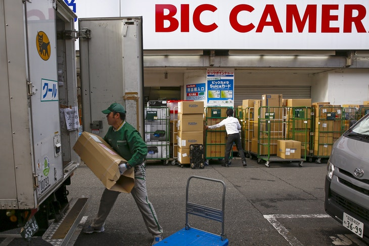 A delivery man loads a parcel into a truck as a staff member organises boxes with consumer electronics outside the Bic Camera retailer in Tokyo