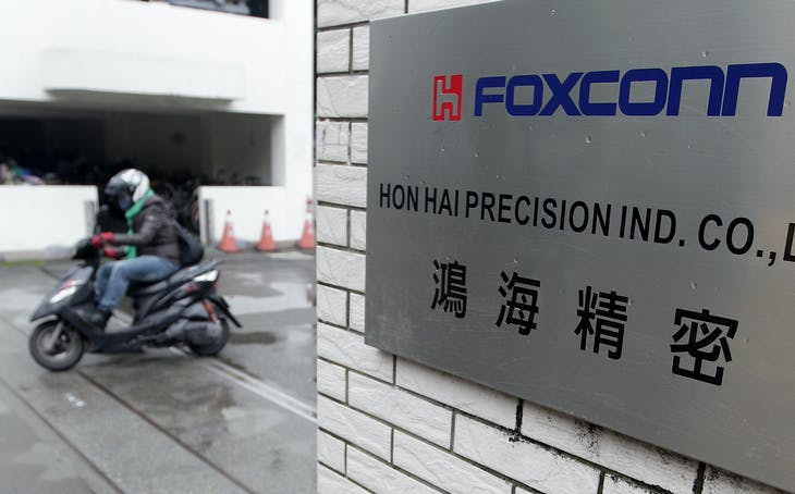 A motorcyclist rides past the entrance of the headquarters of Hon Hai, which is also known by its trading name Foxconn, in Tucheng, New Taipei city, December 24, 2013. Foxconn's BlackBerry Ltd deal marks the Taiwanese firm's biggest step up the value chain - a chance to not just assemble smartphones, but help design them, too.  REUTERS/Pichi Chuang (TAIWAN - Tags: BUSINESS SCIENCE TECHNOLOGY TELECOMS) - RTX16T3M