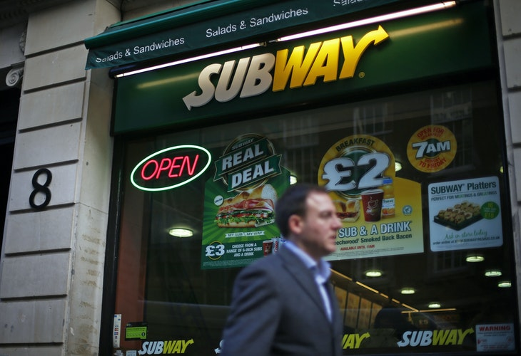 A man walks past a Subway sandwich store in central London