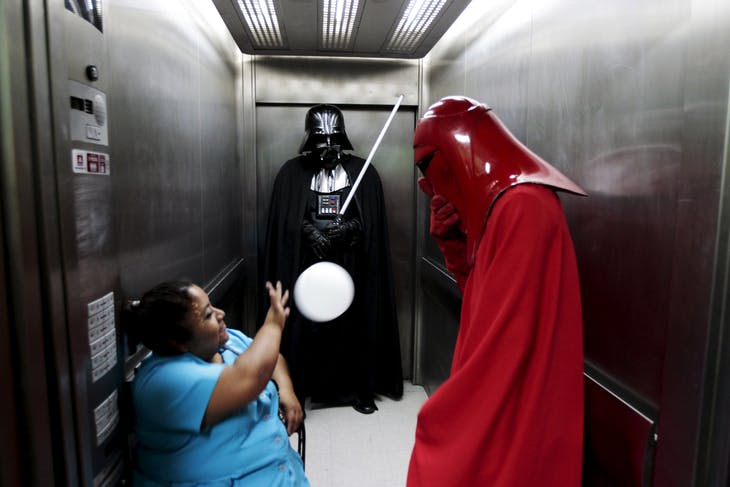 Cosplayers dressed as characters from the Star Wars movie series joke with an elevator operator during a charity event organised by the El Salvador Star Wars fan club at the Benjamin Bloom National Children's Hospital in San Salvador, El Salvador December 14, 2015. REUTERS/Jose Cabezas - RTX1YOG0