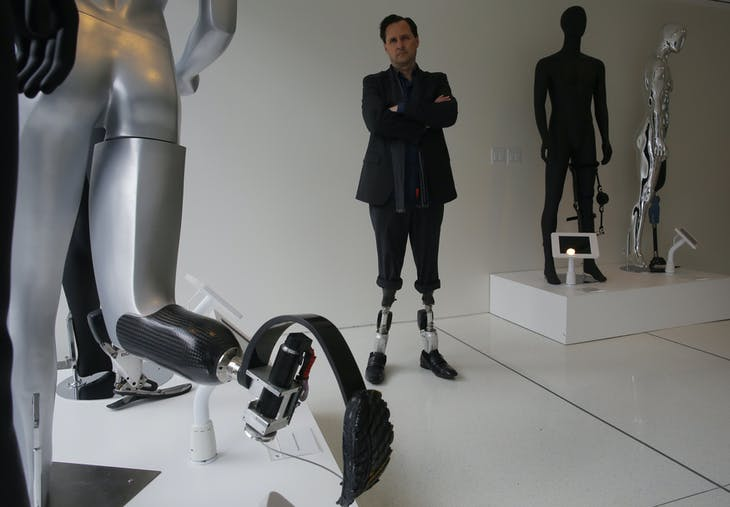 Professor Hugh Herr, who heads the Biomechatronics research group at the MIT Media Lab, stands amid mannequins displaying various bionic limbs his lab has developed at the Massachusetts Institute of Technology in Cambridge, Massachusetts April 4, 2014. The homemade bombs that ripped through the crowd at the finish line of last year's Boston Marathon, killing three people and injuring 264, showcased the city's medical talent but also taught valuable lessons in responding to a mass disaster. As victims slowly adjust to life without limbs, a ballroom dance instructor's story inspired the Massachusetts Institute of Technology biophysicist who is a double amputee to return her to the dance floor with a specially designed bionic leg. Picture taken April 4, 2014.  REUTERS/Brian Snyder  (UNITED STATES - Tags: SPORT ATHLETICS) - GM1EA4H1J5Z01