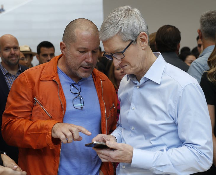 Apple CEO Tim Cook (R) plays with an iPhone as Jonathan Ive, Apple's Chief Design Officer, looks on during a launch event in Cupertino, California, U.S. September 12, 2017. REUTERS/Stephen Lam - HP1ED9C1JSRDS
