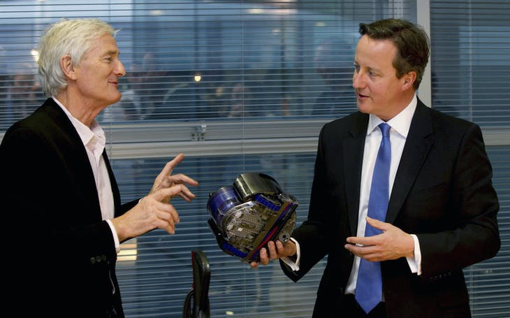 Britain's Prime Minister David Cameron (R) views vacuum design products with James Dyson at the Dyson headquarters in Malmesbury , south west England, November 21, 2014. REUTERS/Newsteam/Pool (BRITAIN - Tags: POLITICS BUSINESS) - GM1EABM07L601