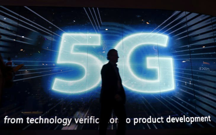 A visitors walks past a 5G sign during Mobile World Congress in Barcelona, Spain, February 28, 2017. REUTERS/Eric Gaillard - RC1FED28BDE0