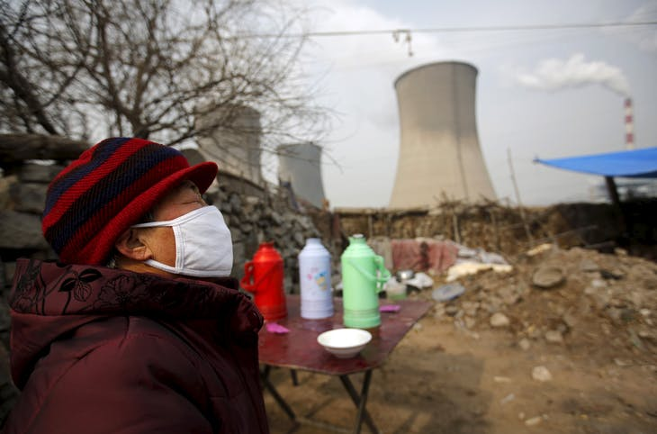 A woman wearing a mask reacts at her garden which  locates next to chimneys of coal-fired power plant in Shijiazhuang, Hebei province, China,  January 28, 2015. Beijing introduced tougher regulations this year to combat pollution, keen to overhaul China's unwanted image of smog-choked cities, fouled waterways and heavy-metal tainted soil.  Picture taken on January 28, 2015.   REUTERS/Kim Kyung-Hoon   - GF10000103372