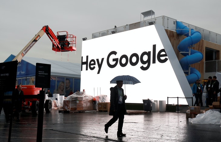 A man walks through light rain in front of the Hey Google booth under construction at the Las Vegas Convention Center in preparation for the 2018 CES in Las Vegas, Nevada, U.S. January 8, 2018. REUTERS/Steve Marcus - RC1AD2102DC0