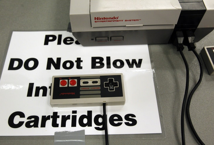 A sign taped next to an old Nintendo system reads, 'Please Do Not Blow Into The Cartridges' at the PAX East gaming conference in Boston, Massachusetts April 7, 2012. REUTERS/Jessica Rinaldi (UNITED STATES - Tags: SCIENCE TECHNOLOGY SOCIETY) - GM1E8480OT801