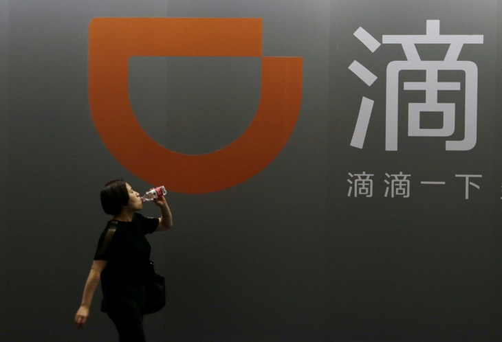 A woman walks past Didi Chuxing's booth at the Global Mobile Internet Conference (GMIC) 2017 in Beijing, China April 28, 2017. REUTERS/Jason Lee - RC15C1684500
