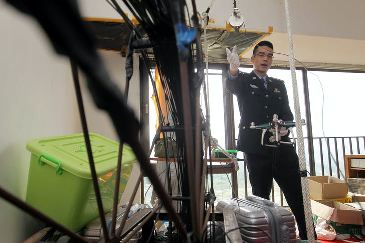A customs officer speaks at the crime scene after authorities arrested suspects who used drones to smuggle smartphones from Hong Kong to Shenzhen, in Shenzhen, Guangdong province, China March 29, 2018. Picture taken March 29, 2018. Liu Youzhi/Southern Metropolis Daily via REUTERS  ATTENTION EDITORS - THIS IMAGE WAS PROVIDED BY A THIRD PARTY. CHINA OUT. - RC15D1A494E0