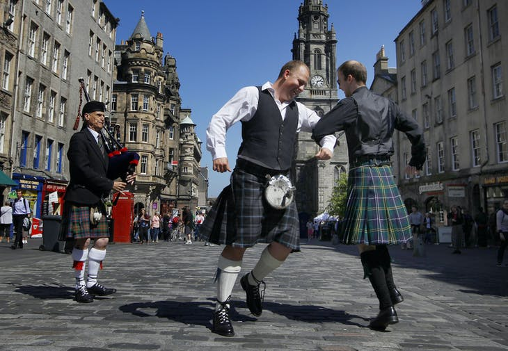 Andy Lang (R) and Liam Reid dance together, wearing kilts while on their way to a wedding, as bagpiper Richard Macdonald plays in the Royal Mile in Edinburgh, Scotland May 25, 2012. Supporters of independence for Scotland launched the 'Yes Campaign' on Friday with what they say is the biggest grassroots campaign in Scottish history, a move that could result in the demise of a 305-year-old union with England and the breakup of Britain. REUTERS/David Moir (BRITAIN - Tags: POLITICS) - LM1E85P14BC01