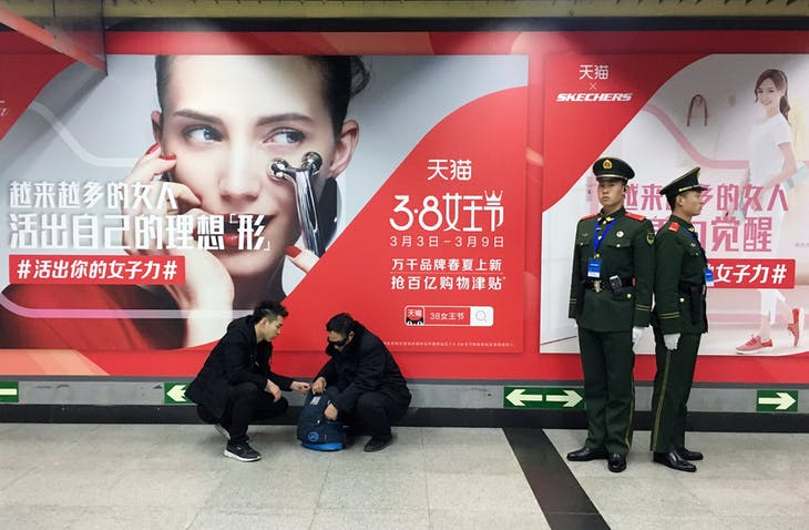 Paramilitary police officers stand in front of an International Women's Day advertisement by Tmall, Alibaba's e-commerce platform, at a subway station in Beijing, China March 7, 2018. Picture taken March 7, 2018. REUTERS/Jason Lee - RC1D467025B0