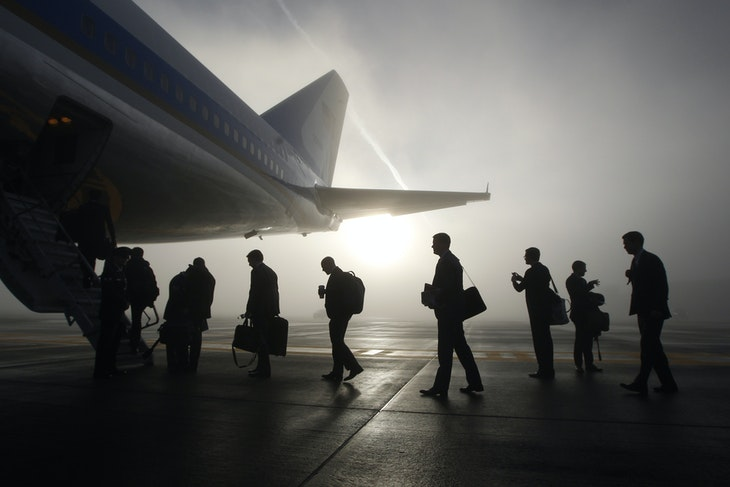 Travelling White House staff and press board the rear steps of Air Force One on a foggy morning in Seattle, November 25, 2013. U.S. President Barack Obama is attending fundraisers and events on the economy and immigration in Los Angeles and San Francisco on Monday.     REUTERS/Jason Reed   (UNITED STATES - Tags: POLITICS TPX IMAGES OF THE DAY) - GM1E9BQ02UK01