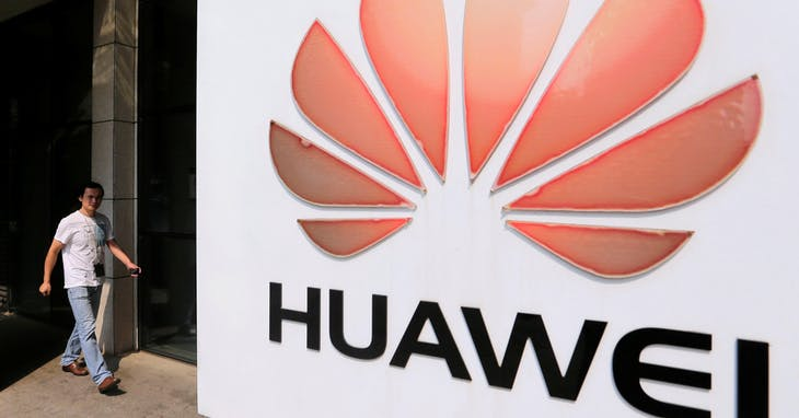 FILE PHOTO:  A man walks past a Huawei company logo outside the entrance of a Huawei office in Wuhan, Hubei province October 9, 2012.  REUTERS/Stringer/File Photo - RC17E21F4000